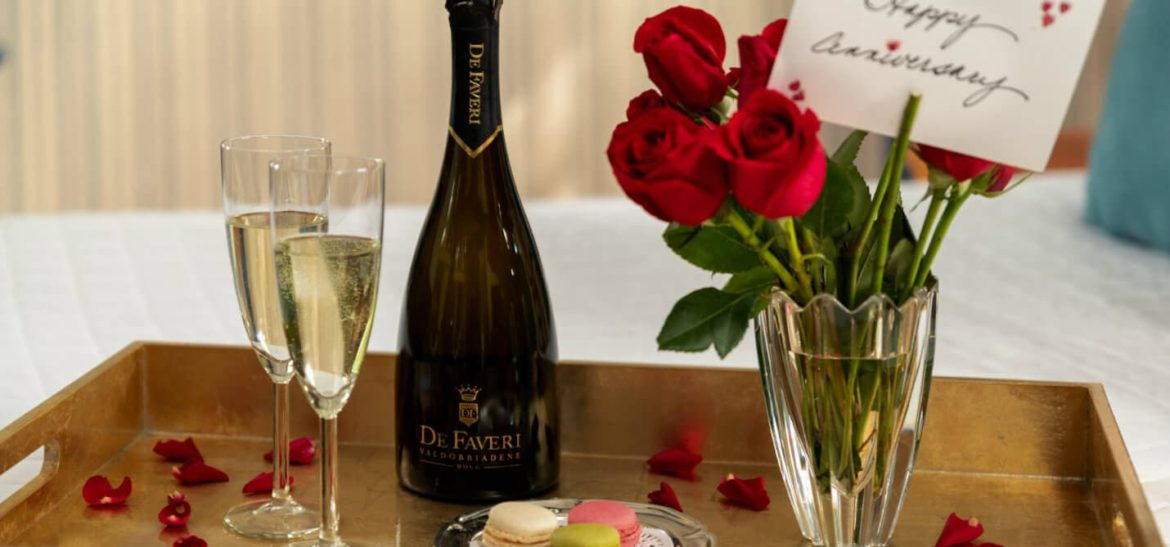Prosecco, flutes, roses and macaroons on a tray