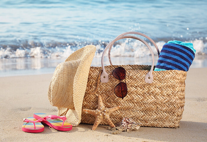 Beach bag with towel, hat, sunglasses, and shoes at a top Kennebunkport beach
