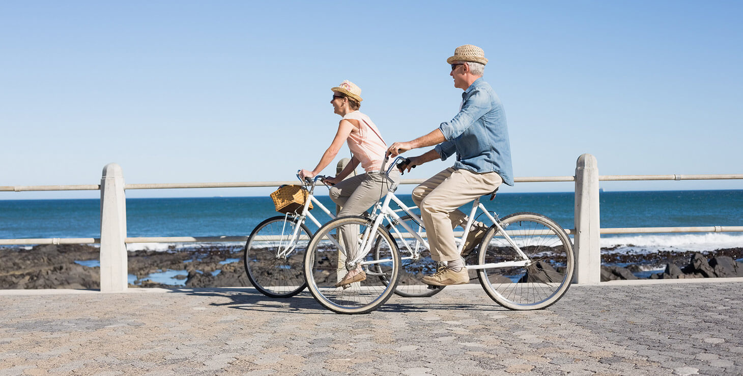 Couple biking together by a Kennebunkport beach