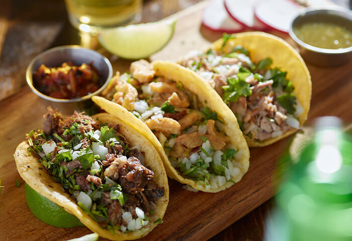 Street tacos on a wooden plate