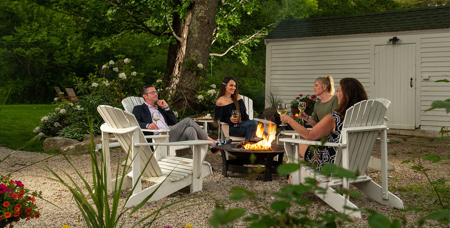 Friends relaxing by the firepit at our romantic Kennebunkport, Maine bed and breakfast