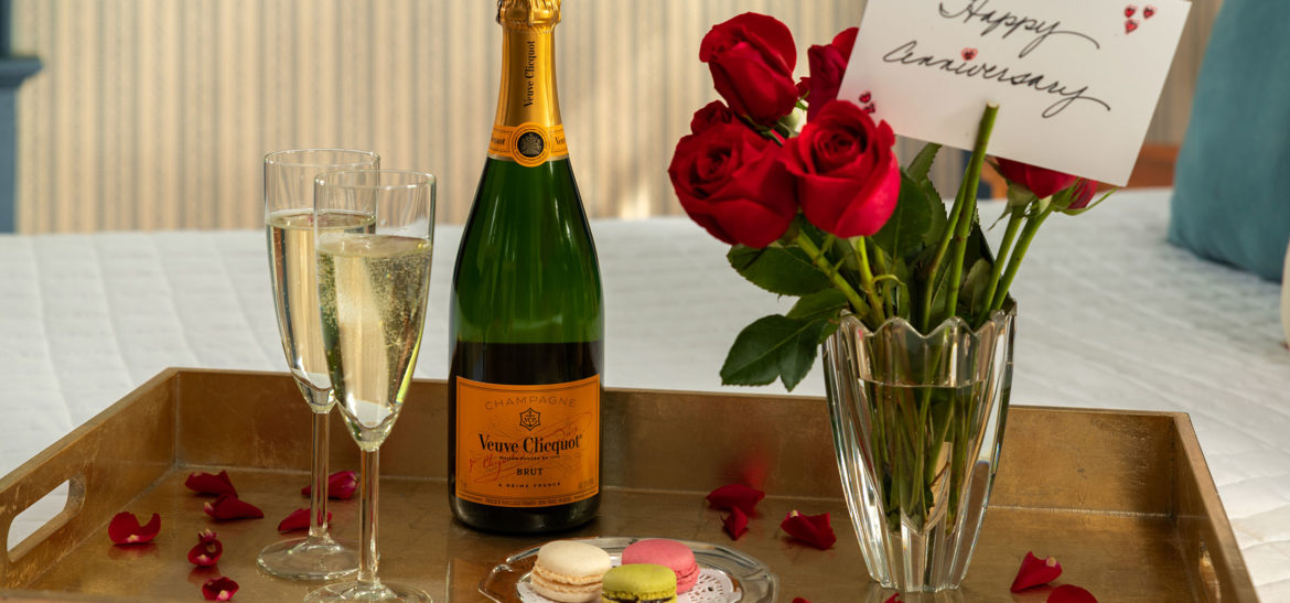 Luxury celebration package with champagne, cake, and flowers