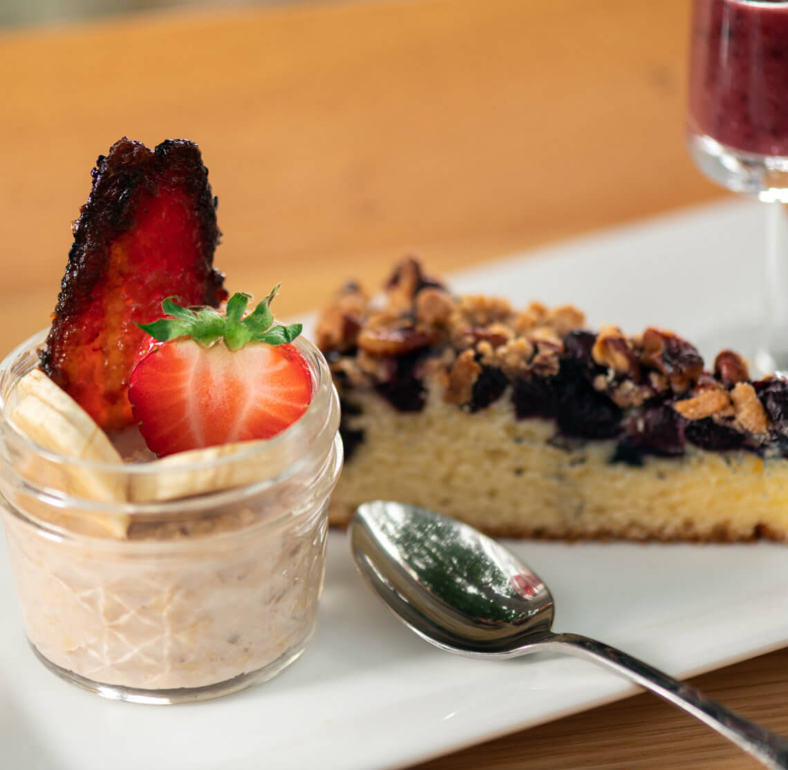 Fruit in a cup with yogurt, blueberry crumb cake and a shiny silver spoon