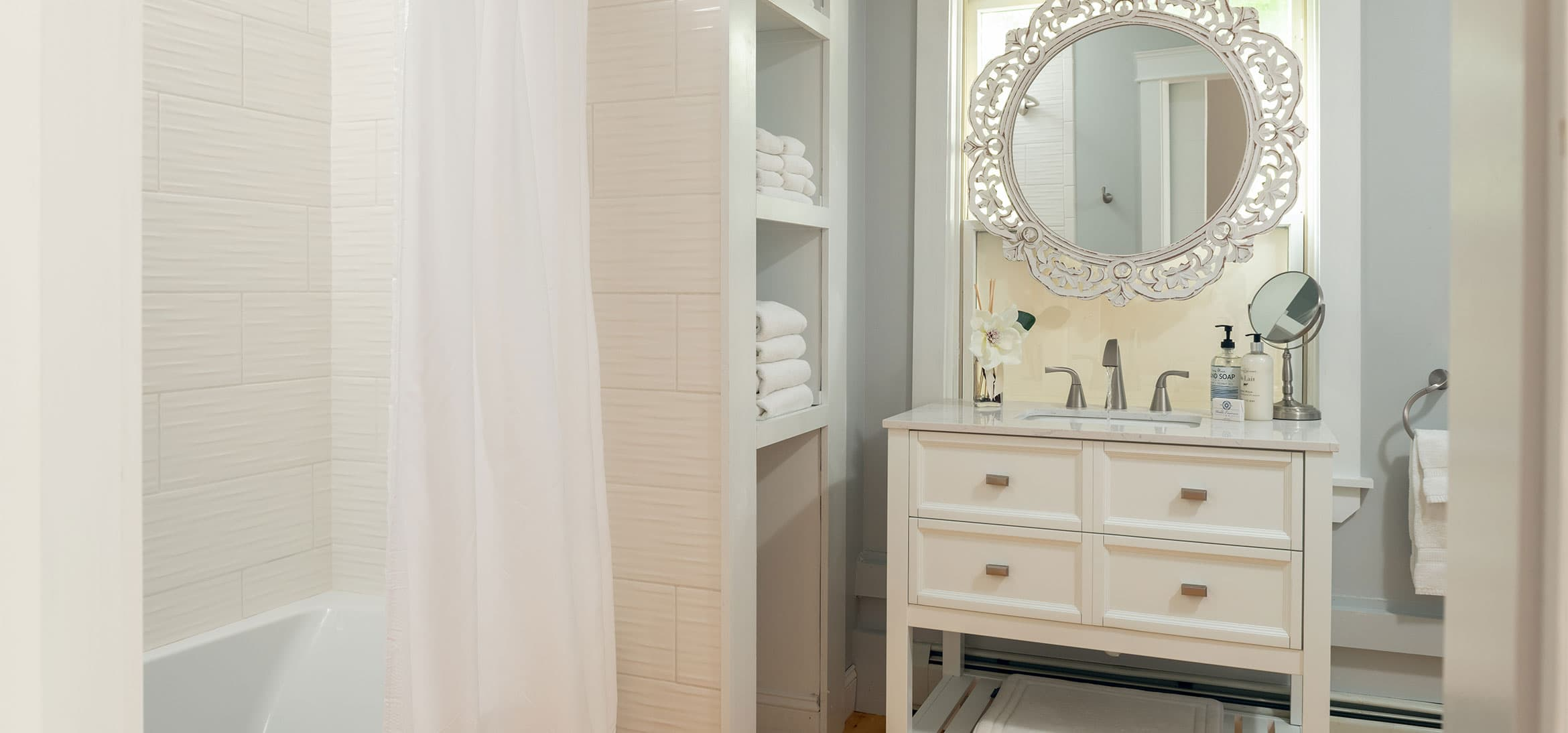 Bathroom with a ornate round mirror, vanity sink, a tub and shower