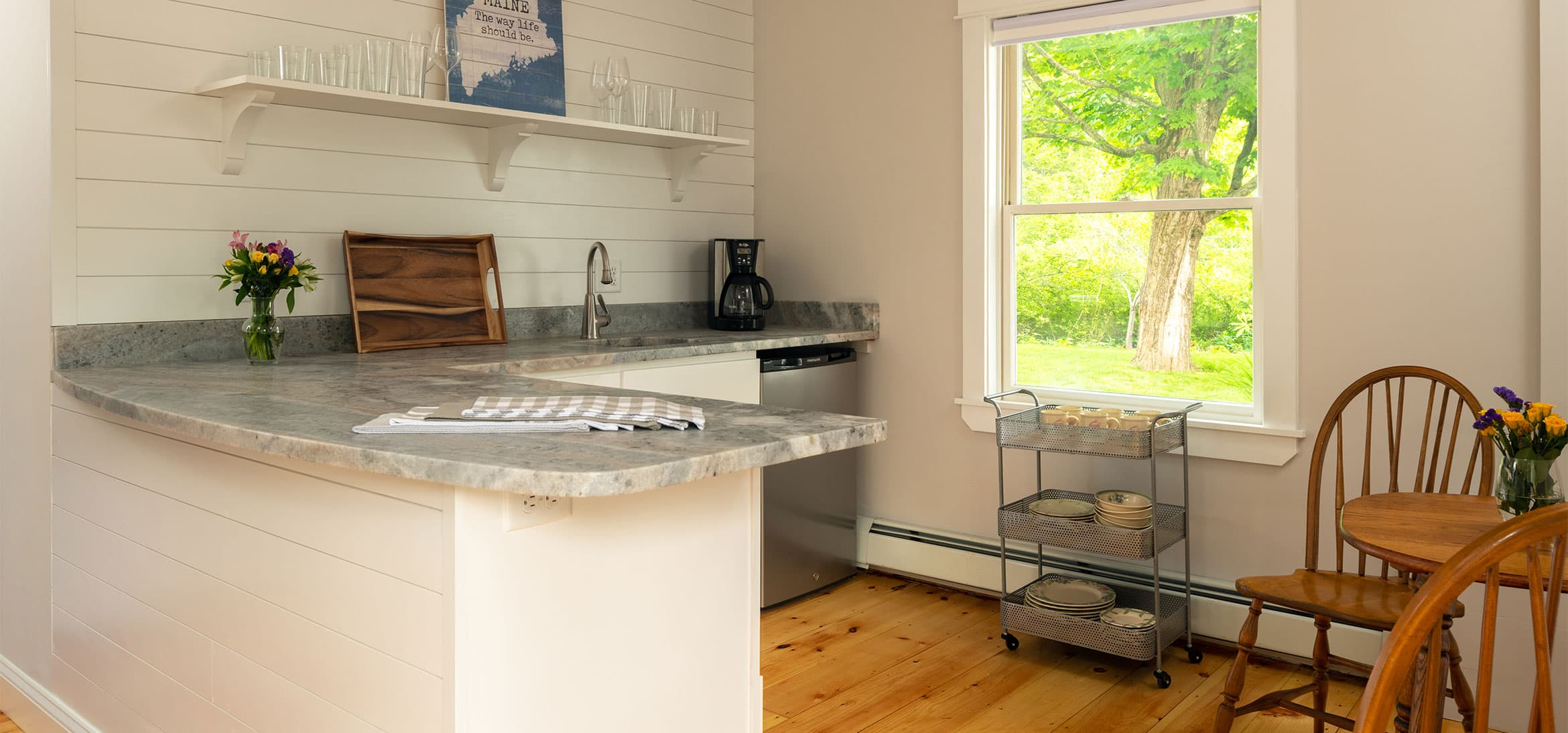 A complete L-shaped kitchen with a dining table and window with a garden view
