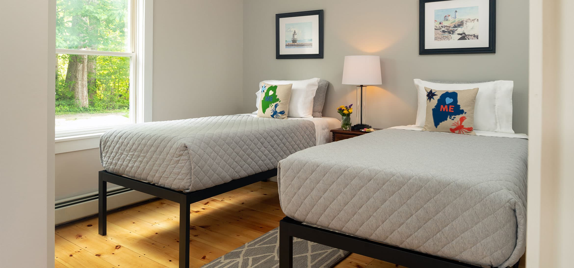 Two twin beds in a room with a bedside lamp